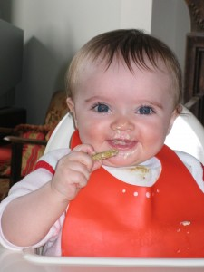 Babybear enjoying her first oatcake with hummus